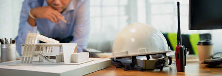 Engineer or Architecture design. Thinking in architecture and building structure modern box house while looking to model on desk office. Selection focus on the home model. Banner with copy space.