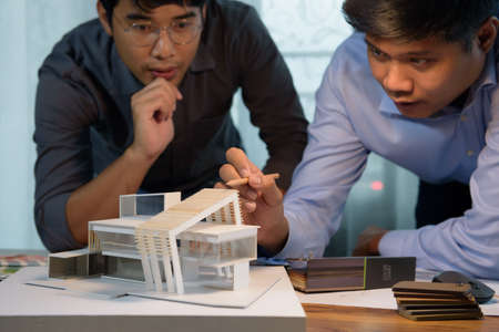 Asian architects discussing with designer or civil engineer about concept of building design and construction project for modern box house. Focusing on the house model.