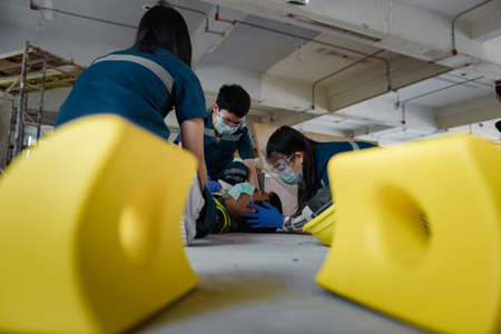 Emergency Medical First aid for head injuries of worker accident in work, Loss of feeling or loss of normal movement and Loss of function in limbs, First aid training to transfer patient.