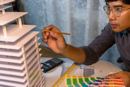 Architect-designer working at night with model of hight building while thinking about concept of building and construction project before startup in the future.