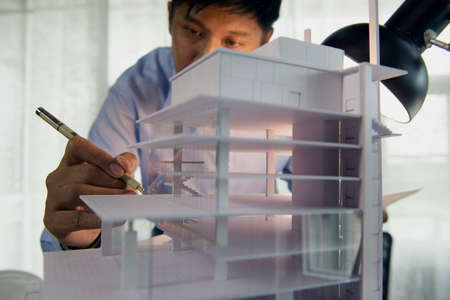Architects worked thinking design architecture with building model, Design from his idea stationery on desk office. Startup and analysis of the architecture of building structure.