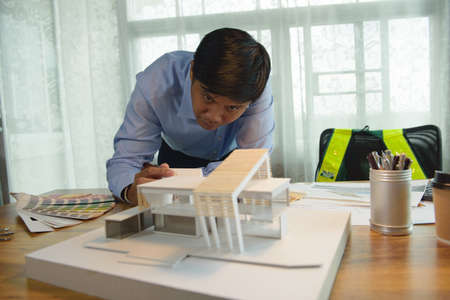 Architect-designer working with model of modern box house while thinking about concept of building and construction project before startup in the future. 免版税图像