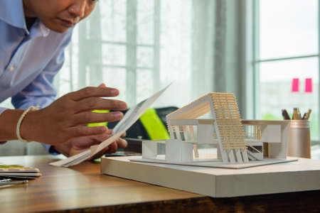 Architect-designer working with model of modern box house while thinking about concept of building and construction project before startup in the future. Focusing on model. 免版税图像