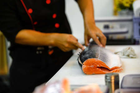 Fresh salmon fillet close-up on white cutting board table while filleting or slicing by chef in cooking room. Selection focusing on salmon fillet with Soft focusing shooting.