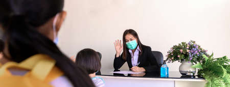 Teacher screening and records data of kindergarten students before entering the classroom for Coronavirus prevention. New social interaction as part of the transition from home to school. 免版税图像
