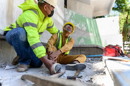 Builder worker has an accident at work. His feet stepped on nails embedded in wood old with foreman rushed in to take care. First aid and Safety in work concept.