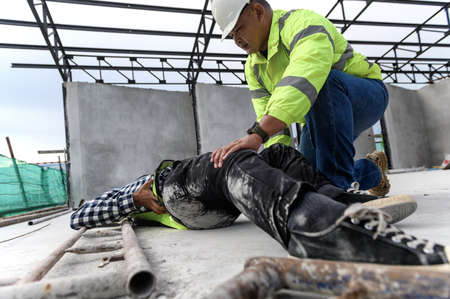 Accident at work of construction worker at site. Builder accident falls scaffolding on floor, First aid team rushed in to take care prepare helps employee accident. Safety in work concept.