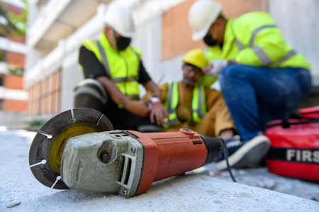 Hand of builder worker injury bleeding, accident in work, Using construction power tools unsafe and negligence with first aid team support at construction site. Selection focus on power tools. 免版税图像