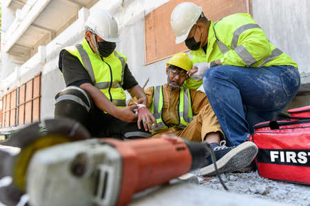 First aid team support to builder worker after hand injury bleeding, accident in work, Using construction power tools unsafe and negligence at construction site. Safety in work concept.