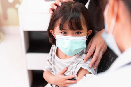 Asian little girl wearing face mask looking doctor holding syringe subcutaneous vaccinated in doctor's office or Pediatric clinic service. Syringe with vaccine protective coronavirus, covid-19
