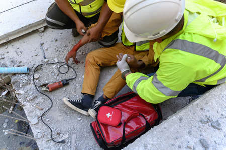 Hand of builder worker injury bleeding, accident in work, Using construction power tools unsafe and negligence with first aid team support at construction site. Safety in work concept.
