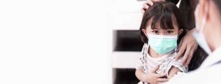 Asian little girl wearing face mask looking doctor holding syringe subcutaneous vaccinated in doctor's office service. Syringe with vaccine protective coronavirus, covid-19 Banner with copy space. 免版税图像