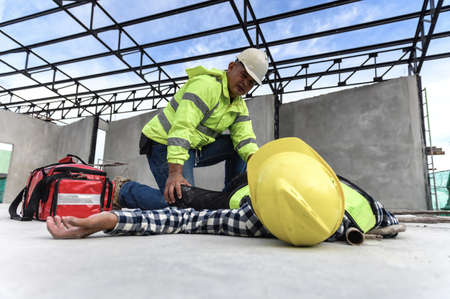 Heat Stroke or Heat exhaustion in body while outdoor work. Accident at work of builder worker at Construction site. Check Response, Lifesaving, and rescue, first aid basic concept. 免版税图像