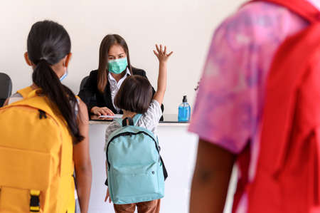 Kindergarten student girl raising her hand and personal information report with Teacher, Social interaction. Screening of preschool students before entering a classroom for Coronavirus prevention.