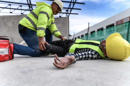Heat Stroke or Heat exhaustion in body while outdoor work. Accident at work of builder worker at Construction site. Selection focus on hand of worker, Lifesaving, rescue, first aid basic concept.