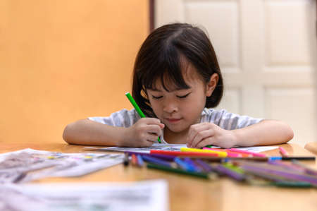 Asian little girl sitting practice their skills and focus on coloring paper on table. Preschoolers learning at home to write and reading, Art education and creativity, Children's activities.