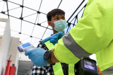 Labour Screening, Construction foreman wearing protective face mask pointing measurement results of body temperature of welder worker in an Infrared Thermometer during  Pandemic