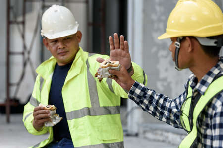 Asian builder workers in uniform are eating while sitting break time and not eating together for social distance and preventing the epidemic of  virus and Lunch of worker concept.