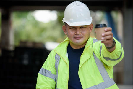Construction engineer in reflective unifrom safety holds a cup hot coffee and hand to camera before work begins. Foto de archivo