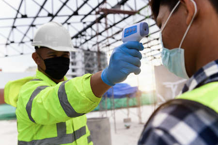 Construction foreman wearing protective face mask screening body temperature of worker with Infrared thermometer before start work in building construction area during Pandemic Foto de archivo