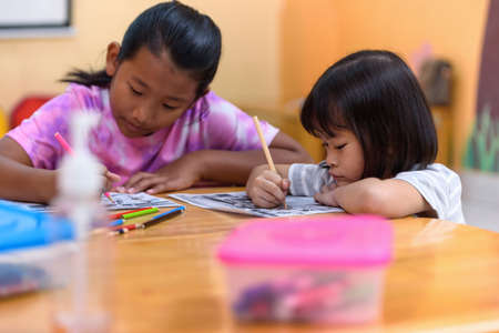 Asian little girl group sitting practice their skills and focus on coloring paper on table. Preschoolers learning at home to write and reading, Art education and creativity, Children's activities.