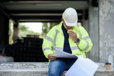 Civil Engineer sitting eats small bread in break time and reading building drawing with construction materials stock in background while hot weather at construction site during the day.