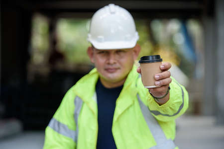 Construction engineer in reflective unifrom holds a cup hot coffee and hand to camera before work begins. Selection focuses on the cup of coffee.