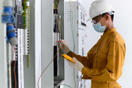 Electrician engineer using digital multimeter test current electric in control panel for testing electrical installations and wiring work in power control room on new building.