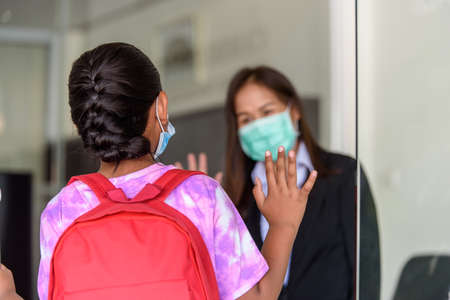 Student girl kids in medical face mask and raising their hand to greet teacher at Tutor school entrance door, Student screening before walk in classroom. Foto de archivo