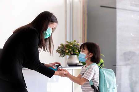 Teacher giving hand sanitizer alcohol gel and helping students stay clean for healthy and clean at school. Student screening before walk in classroom.