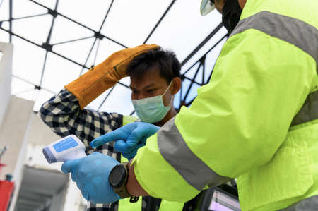 Labour Screening, Construction foreman wearing protective face mask pointing measurement results of body temperature of welder worker in an Infrared Thermometer during Pandemic Foto de archivo