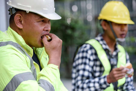 Asian builder workers in uniform are eating while sitting break time and not eating together for social distance and preventing the epidemic of  and Lunch of worker concept. Foto de archivo