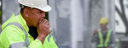 Asian builder worker sitting eats small bread in break time while hot weather during the day at construction site, Minimum wage, Labor poverty, Support oneself. Banner with copy space Foto de archivo