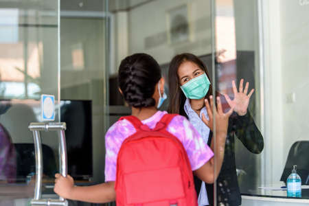 Teachers in medical face mask and raising their hand to greet student girl kids at Tutor school entrance door, Student screening before walk in classroom. Foto de archivo