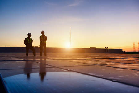 Technician Team checking Photovoltaic cells panels on factory roof, Maintenance of the solar panels, Engineer service, Inspecor concept. Silhouette Photo.