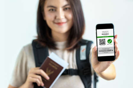 Disease immunity passport, Tourist uses of application on smartphone to show an international certification of vaccination at airport with Immunity passport and vaccination record card for covid-19 Foto de archivo