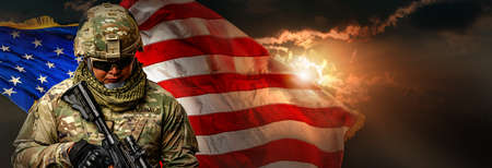 US Army soldier in combat uniforms holding machine gun on the national US flag with gold sunlight background in banner size. Veterans Day, Patriot concept and Independence Day, ID4. Foto de archivo