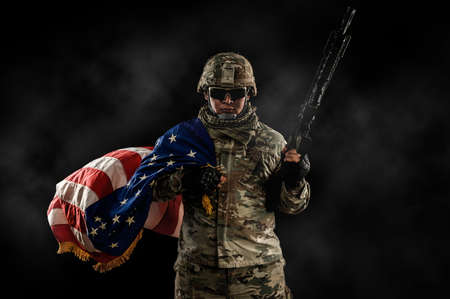 US Army soldier in combat uniforms holding the national flag across the shoulder and machine gun in smoke on dark background. Veterans Day, Patriot concept and Independence Day (United States) or ID4 Foto de archivo