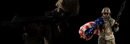 US Army soldier in combat uniforms holding the national flag across the shoulder and machine gun in smoke on dark background with silhouette soldier. Veterans Day, Patriot concept in banner size. Foto de archivo