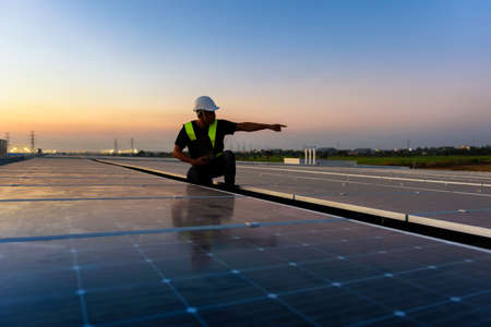 Technician checking Photovoltaic cells panels on factory roof, Maintenance of the solar panels, Engineer service, Inspecor concept. Silhouette Photo.