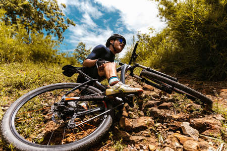 Cyclist accident falling off mountain bike and knee injury at MTB track. Athlete accident in crash and dangerous on trail in forest.