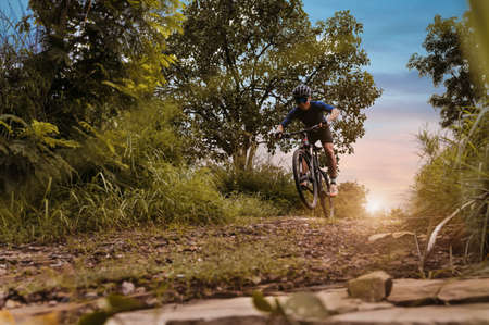 Mountain biking, Cyclist speeding downhill on MTB track in forest with mountain bike, Outdoor sport activity fun and enjoy riding. Basic techniques training for safe on the trail of athlete.