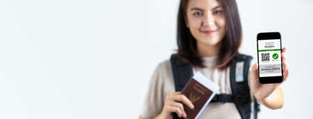 Tourist uses of application on smartphone to show an international certification of vaccination at airport with Immunity passport and vaccination record card  , Disease immunity passport.