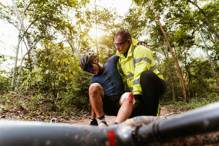Cyclist accident falling off mountain bike and knee injury and first aid at MTB track. Athlete accident in crash and dangerous on trail in forest.