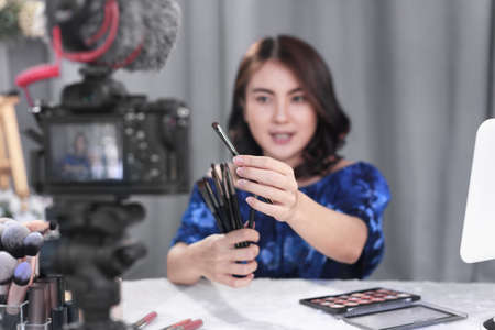 Asian woman beauty blogger recording an easy guide for beginners of cosmetic brushes with makeup product and sharing on social media online with digital camera at home. Selective focus on brushes