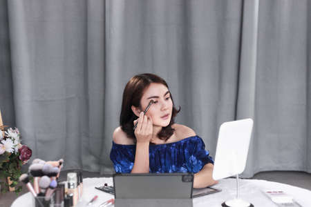 Asian woman beauty blogger recording an easy guide for beginners of cosmetic brushes with makeup product and sharing on social media online with tablet at home. Selective focus on brushes