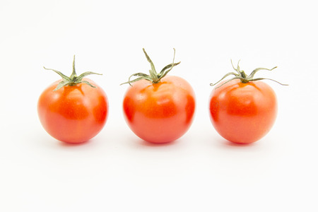 straight line: Straight line tomatoes with green leaf on white background