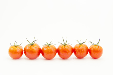 straight line: Fresh drops tomatoes in straight line on white background