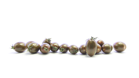 straight line: Fresh black tomatoes mixed size in straight line on white background Stock Photo