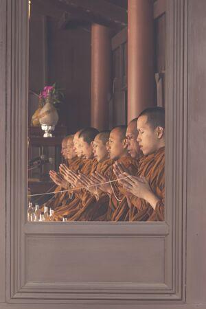 buddha image: Monk start praying in buddha image making ceremony view from window frame